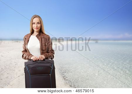 Woman with a suitcase on the sea beach