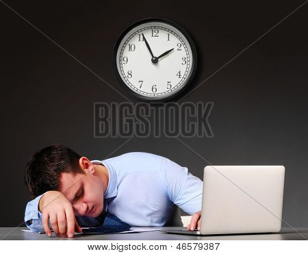 tired businessman is sleeping at his table with laptop