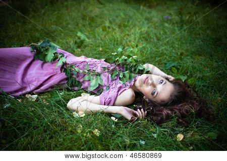 beautiful young woman in purple dress lie in green grass summer day