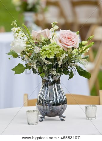 flower arrangement in old silver pitcher