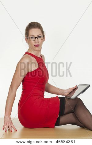 Seductive Woman Wearing A Red Dress With A Tablet