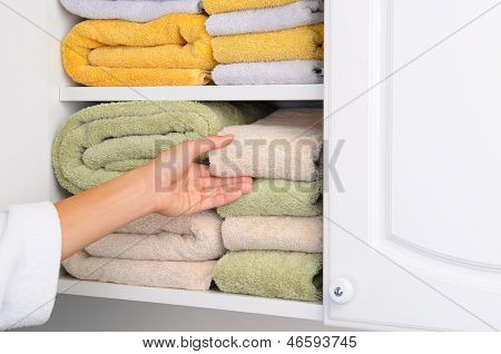 Closeup of a womans hand taking a towel from a linen closet. Arm is partially covered by her bathrobe. Horizontal format.