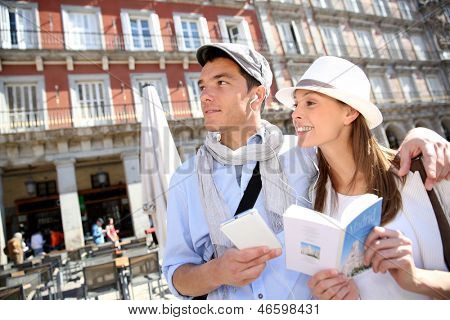 Tourists walking in La Plaza Mayor with traveler guide