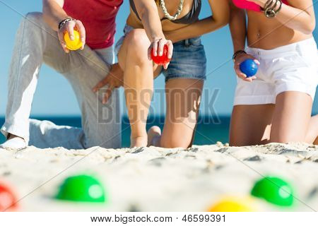 Group of young people playing boule on beach in sand outdoors in summer