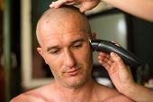 foto of trimmers  - Hairdresser shaving man with hair trimmer - JPG