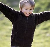 pic of character traits  - Young boy smiling and running with arms outstretched outdoors - JPG