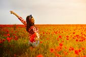 Young beautiful woman walking and dancing through a poppy field, summer outdoor. Toned.