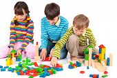pic of children playing  - Three young children playing with wooden blocks - JPG
