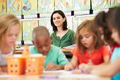 stock photo of 6 year old  - Group Of Elementary Age Children In Art Class With Teacher - JPG