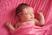 stock photo of headband  - An overhead view of a sleeping 8 day old newborn baby girl wearing a pink flower headband - JPG