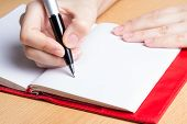 stock photo of ballpoint  - hand of young woman taking notes in notebook - JPG