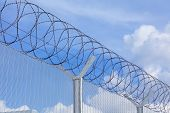 image of chain link fence  - Chain link fence with barbed wire under blue sky - JPG