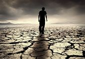stock photo of global-warming  - A young man walks into the desolate desert - JPG