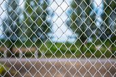 stock photo of chain link fence  - Metallic Wire Chain Link Fence at the farmland - JPG