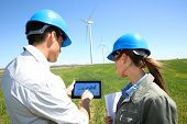 stock photo of turbines  - Engineers using tablet on wind turbine site - JPG