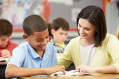 stock photo of pupils  - Teacher Reading With Male Pupil In Class - JPG