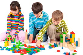 stock photo of children playing  - Three young children playing with wooden blocks - JPG