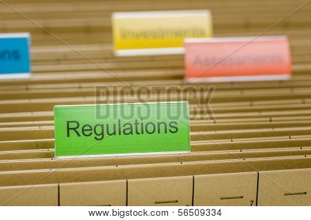 A hanging file folder labeled with Regulations