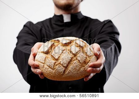 Priest Holding Loaf Of Bread