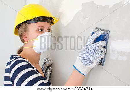 Female Plasterer In Hard Hat Polishing The Wall.