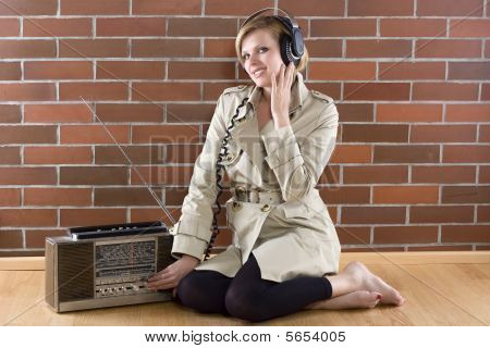 Women In Trenchcoat Listens To A Vintage Radio