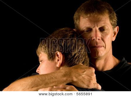 Father hugs son