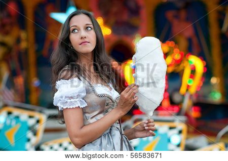 German Girl wearing a traditional Dirndl and eating candyfloss