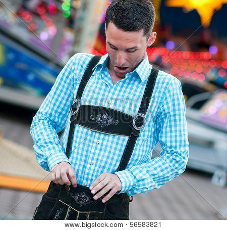 Funny bavarian man checking his lederhosen trousers