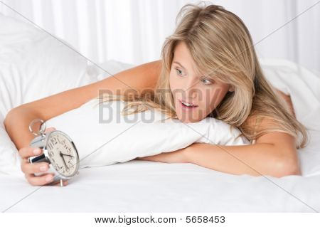 Young Woman Surprised Holding Alarm Clock