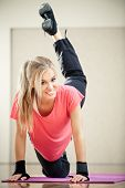 picture of leg-split  - Smiling female fitness instructor in a gym - JPG
