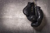 stock photo of knockout  - Retro boxing gloves hanging on a grungy background - JPG