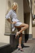 stock photo of streetwalkers  - blonde beautiful woman stands near wall of building - JPG