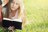 Young Teenage Girl Reading Book On Grass