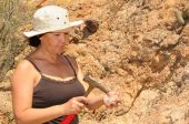stock photo of paleontologist  - Senior woman geologist tap a rock formation with a hammer - JPG