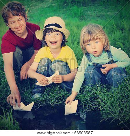 three boy play in  stream