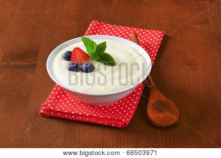 sweet semolina pudding with fresh fruit, served in the bowl with dotted napkin