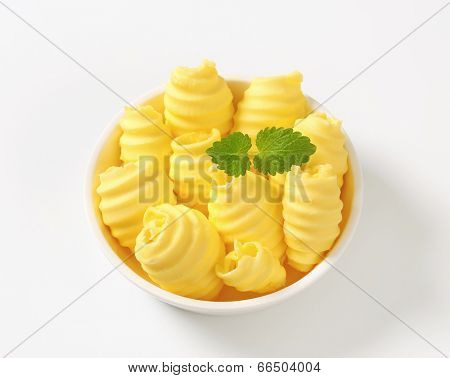 yellowish butter curls decorated with piece of herb