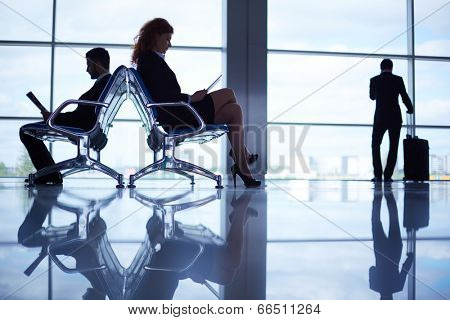 Two business partners reading at the airport on background of their colleague with suitcase by the window