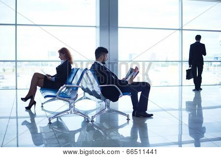 Two business partners reading at the airport on background of their colleague standing by the window