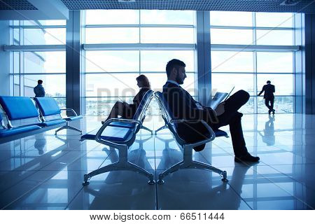 Two business partners reading at the airport on background of their colleagues by the window