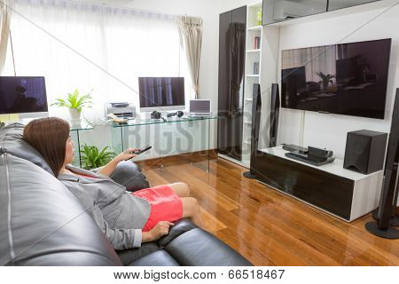 Business young woman watching TV in modern home office with computer and labtop