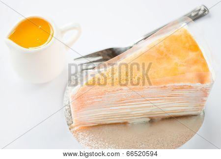 Crepe Cake With Orange Sauce On White Background