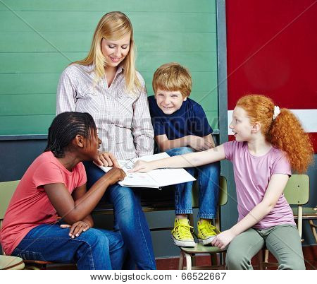 Elementary school students pointing to notebook in class