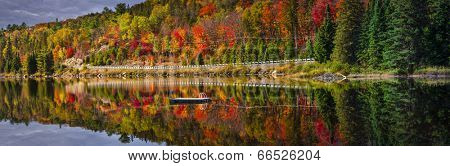 Panorama of scenic route through fall forest with colorful autumn foliage reflecting in lake. Highway 60, Algonquin Park, Ontario, Canada.