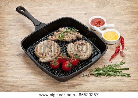 Grilled sausages with ketchup and mustard. Over wooden table background