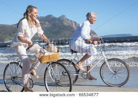 Smiling couple riding their bikes on the beach on a sunny day