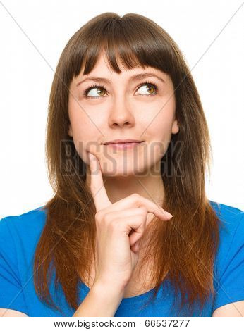 Portrait of a happy young woman thinking about something while touching her cheek with finger, isolated over white