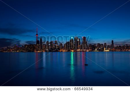 Toronto cityscape at night with reflections over the lake