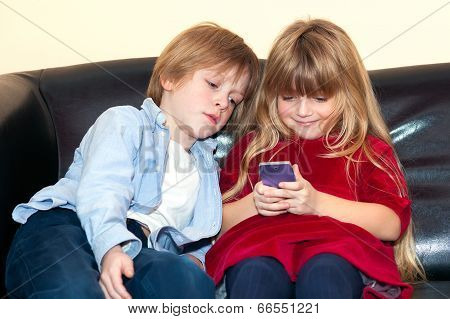 Little Girl Using A Mobile Watched By Her Brother