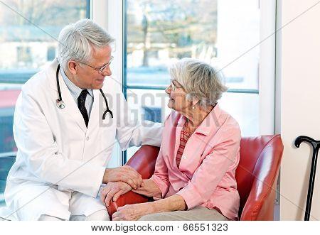 Friendly Doctor Reassuring An Elderly Woman